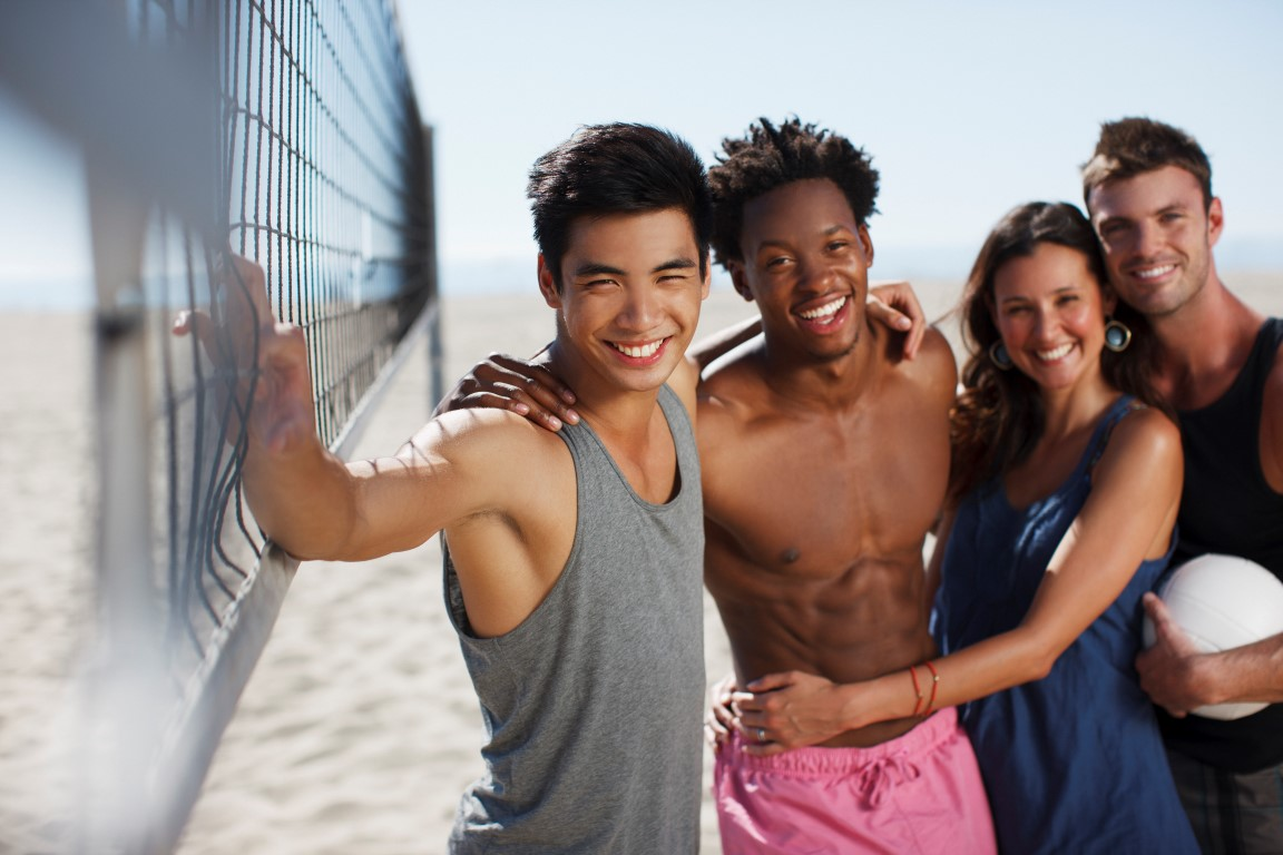Friends smiling on beach volleyball court